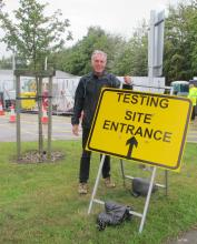 Council Leader standing beside a Covid test site sign