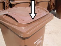 Brown bin with arrow showing where the notch is removed on the left hand side of the lid