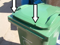 Green bin with arrows pointing to where notches are removed either side of the front of the lid