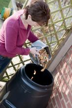 woman emptying food into compost bin